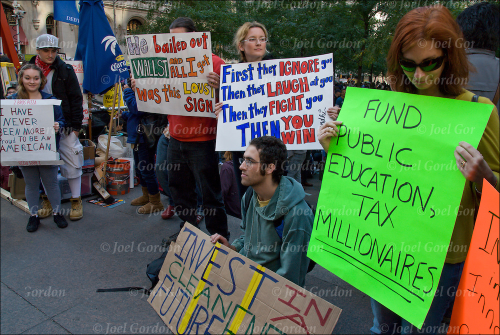 Occupy Wall Street (OWS) prostesters in Zuccotti (Liberty) Park with signs.<br /> <br /> This is a grassroots, nonviolent movement,  made up of multi-generation of all ages and social-economic background. They call themselves  the 99% protesters and are about income equality and social justice issues but remained loosely organized and there were no specific demand.<br /> <br /> They come out for their own reasons rather than the reasons that someone else has given to them. Some protesters  want the movement to rally around a goal, while others insist that isn't the point.