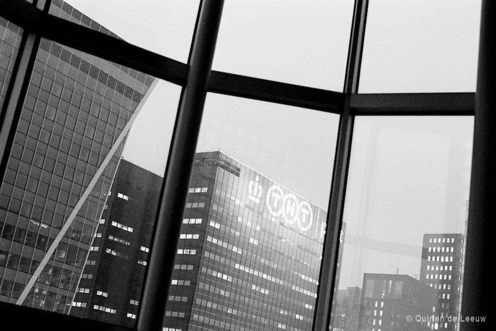 Het TNT gebouw, nu PostNL, in Den Haag. Een van de grote bedrijven binnen Het Systeem. Een bureaucratische organisatie dat te maken heeft met veel reorganisaties, ontslagrondes door een verouderd businessmodel, liberalisering en concurrentie. Digitalisering en de financiële crisis hebben mede gezorgd voor vele veranderingen binnen het bedrijf.