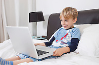 Smiling Caucasian boy using laptop computer in bed