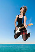 Female guitarist jumps with ocean and sky background