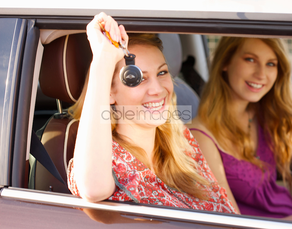 Two young women sitting in a car