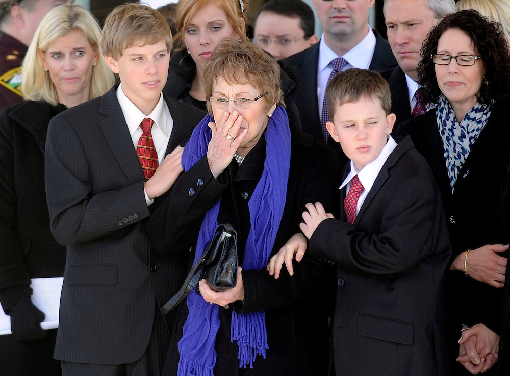 Mary Dean Janklow (center) is comforted and surrounded by family as the flag-draped casket of her husband, Bill Janklow, is placed in the hearse outside of Our Savior's Lutheran Church after his funeral in Sioux Falls. Janklow, 72, died Thursday, Jan. 12, 2012, after a months-long battle with brain cancer.