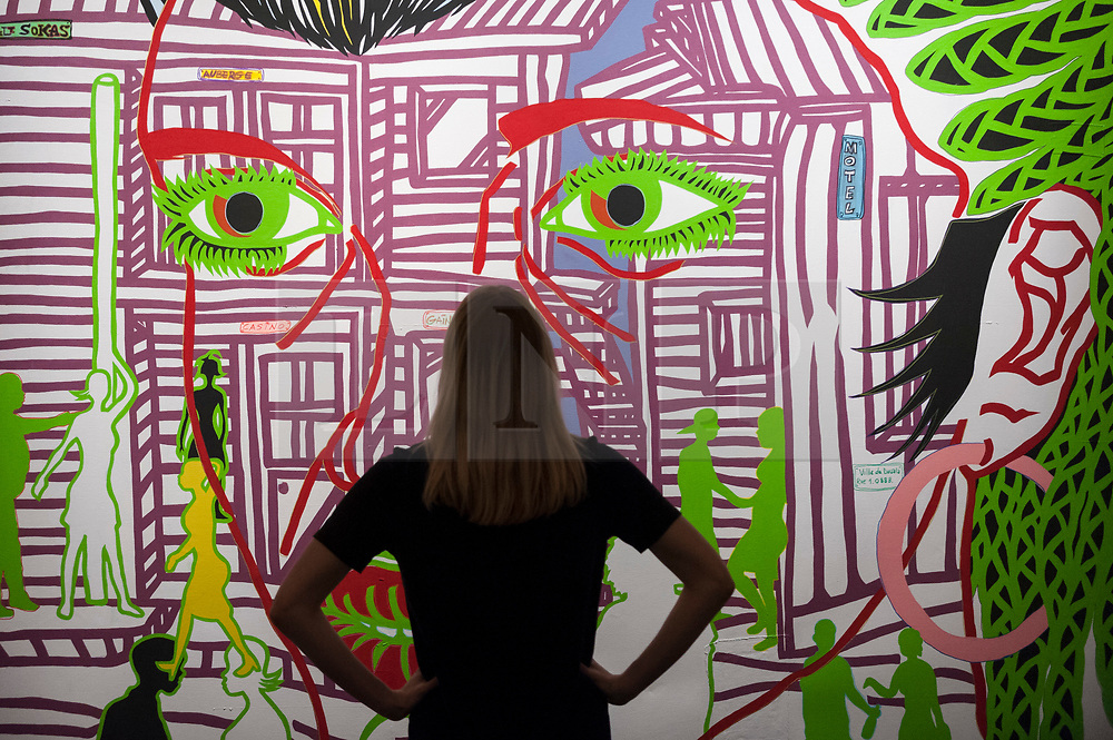 """© Licensed to London News Pictures. 23/03/2018. LONDON, UK. A staff member views """"Douala Tonight"""", 2014, by Boris Nzebo (Est. GBP6,000-9,000).  Preview of Modern and Contemporary African Art sale at Sotheby's, New Bond Street.  The auction will take place on 28 March 2018.   Photo credit: Stephen Chung/LNP"""