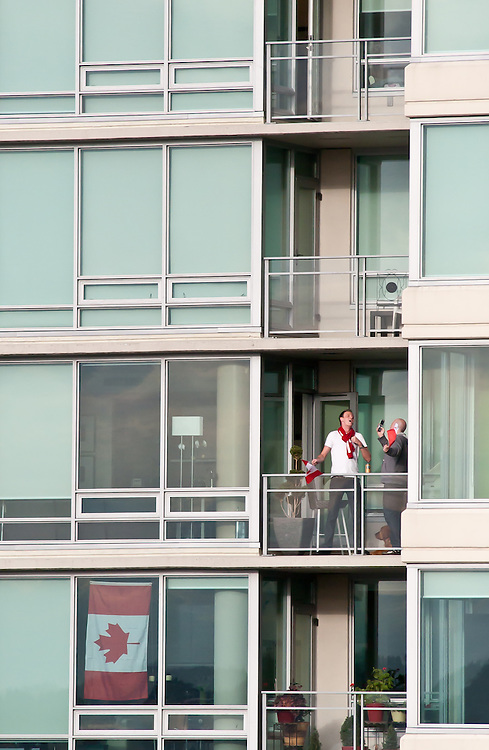 Two friends sing and chant on the balcony of their Downtown appartment in Vancouver West End.<br /> <br /> Tens of thousands of people in Vancouver took to the streets on Sunday 28th February 2010 to celebrate Canada's 3-2 overtime win over the United States for the gold medal in men's Olympic hockey...Traffic came to a halt in and around the downtown of the host city for the Winter Games following the dramatic finish to the match, which featured Sidney Crosby scoring to secure the victory on the final day of Olympic competition.