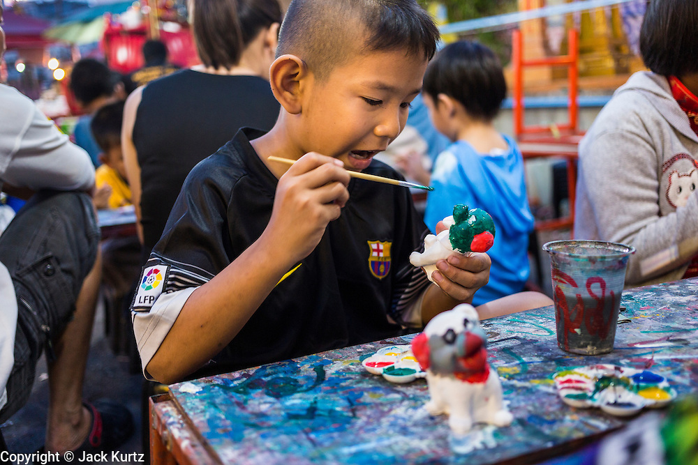 09 FEBRUARY 2014 - HAT YAI, SONGKHLA, THAILAND:  A boy paints a toy in a booth at the street fair during Lunar New Year in Hat Yai. Hat Yai was originally settled by Chinese immigrants and still has a large ethnic Chinese population. Chinese holidays, especially Lunar New Year (Tet) and the Vegetarian Festival are important citywide holidays.     PHOTO BY JACK KURTZ