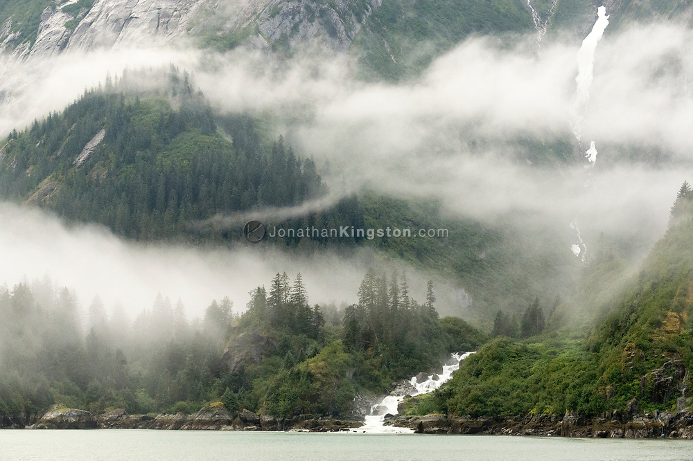 A waterfall and mist shrouded cliffs of Tracy Arm Fjord, Alaska.