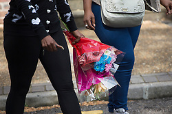 © licensed to London News Pictures. London, UK 30/07/2013. People bringing flowers to the flat where a 29-year-old woman found dead and a 17-year-old with stab wounds at Tilson Gardens, Brixton. A 40-year-old man has been arrested on suspicion of murder after two women and a teenager were stabbed in south London. Photo credit: Tolga Akmen/LNP