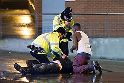 """© licensed to London News Pictures. Manchester UK. 28/11/12 Ministers are to unveil plans later for a minimum price for alcohol in England and Wales as part of a drive to tackle problem drinking. FILE PICTURED DATED: 17/12/2011. Police move a man in to recovery position and wait for an ambulance. Despite freezing temperatures, """"Mad Friday"""" revellers in Manchester enjoy what is traditionally the busiest night of the year for emergency services, before Christmas. Police rush to the aid of a man who has collapsed in the street as worried friends look on. Photo credit: Joel Goodman/LNP"""