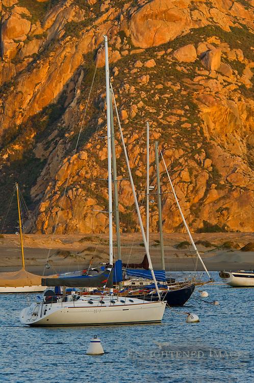 Sailboats anchored in front of Morro Rock at sunrise, Morro Bay, California