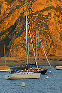 Sailboats anchored in front of Morro Rock at sunrise, Morro Bay, California