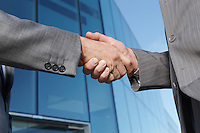 Two business men shaking hands outside office close-up