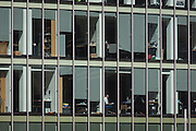 A male employee stares out the window of his office in the City of London.