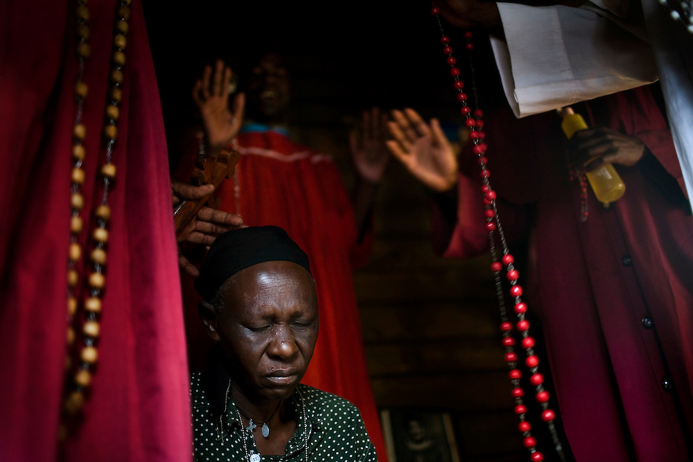 Members of the Legion Maria Church pray for Consolata Anyango, 39, a church member who has HIV and TB. Mathare, one of the poorest slums in Nairobi.  Running water and electricity are scarce and trash and human waste fills the streets.  Many people have no jobs and those who do work can earn less than one dollar a day.