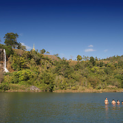 Young children swimming at a temple in Mae Sot Thailand. The temple stands on a hill with a waterfall flowing off the hill and is called Wat Namtok Chedi (Wat Waterfall and Chedi).