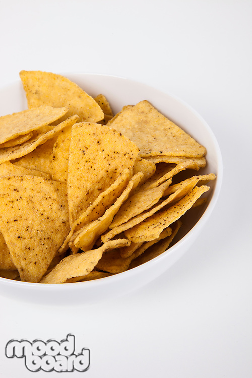 Close-up of nachos in bowl over white background