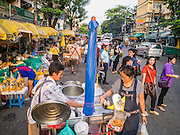 19 OCTOBER 2012 - BANGKOK, THAILAND:   A snack vendor on the street in front of the Bangkok Flower Market. The Bangkok Flower Market (Pak Klong Talad) is the biggest wholesale and retail fresh flower market in Bangkok.  The market is busiest between 3:30AM and 6AM. Thais grow and use a lot of flowers. Some, like marigolds and lotus, are used for religious purposes. Others are purely ornamental.    PHOTO BY JACK KURTZ