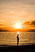 Silhueta de mulher em pé à beira do mar durante o por do sol na Praia do Ribeirão da Ilha. Florianópolis, Santa Catarina, Brasil. / Silhouette of a woman standing by the sea at Ribeirao da Ilha Beach at sunset.