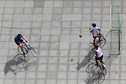 "Boys play bicycle football in a square in Ghent - they ""kick"" the ball with the front tyre of their bikes, but can use their hands to prevent the ball from going into the goal net"