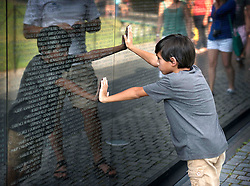 Young boy at Vietnam Memorial. Face to face with the names of soldiers not much older than him who gave their lives in battle.