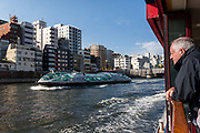 A British tourist watches the distinctive Himiko river-cruise boats from his own Sumida Cruise boats near Asakusa in Tokyo, Japan. Monday April 15th 2019