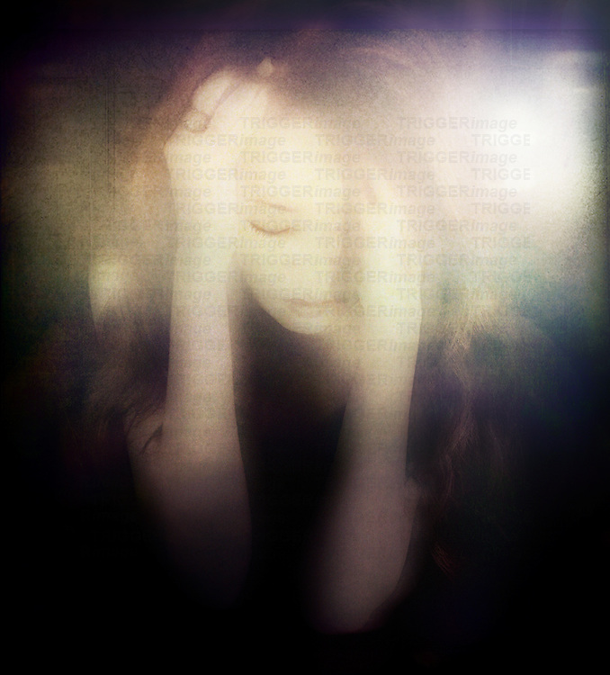 A young woman holding her head in her hands with sad expression