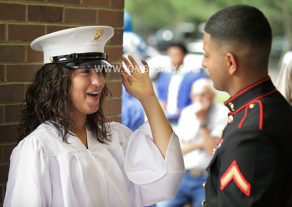 Middletown's Talia Matos smiles after Marine Pfc. Ganesh Bhawgwandeen, a 2010 Middletown graduate, put his hat on her head while they were waiting for the start of Middletown High School's Class of 2012 gradution ceremonies at SUNY Orange in Middletown on Friday, June 22, 2012.