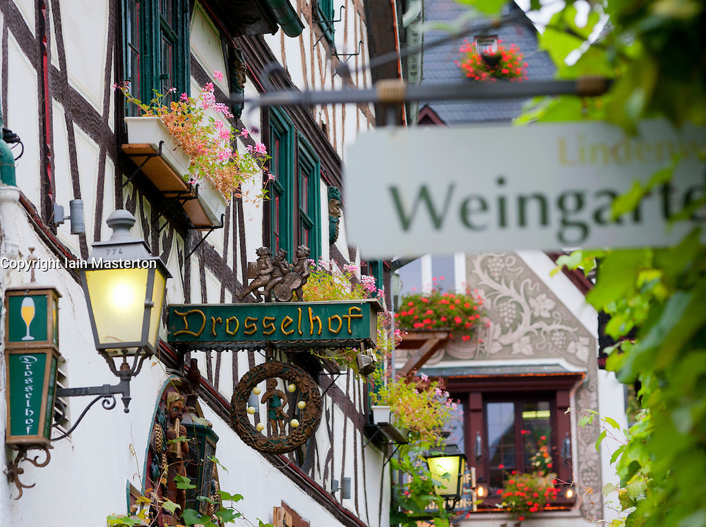 Many signs outside restaurants on famous tourist Drosselgasse Street in popular town of Rudesheim on River Rhine in Germany