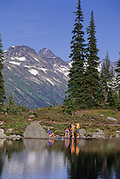 A group of hikers relax by Harmony Lake, Whistler Mountain, BC on a sunny summer day.