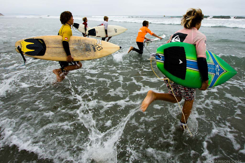 Young surfers run to start the finals of the age 12-13 category of the first annual Grom-o-rama youth surf tournament in Solana Beach, California on August 23, 2008.