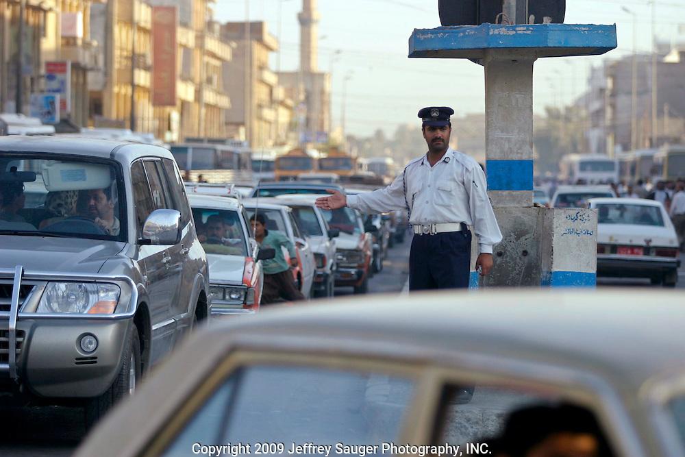 An Iraqi traffic officer directs traffic in Karbala, Iraq, Thursday, July 24, 2003.