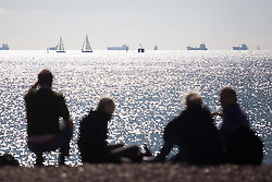 © Licensed to London News Pictures. 02/10/2016. Southsea, Hampshire, UK.  People relax on the beach watching the yachts sail by in the Solent in the warm, sunny weather on another stunning autumn day. Photo credit: Rob Arnold/LNP