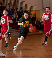 Gilmanton's Brandon Rague dribbles through Nicholas Ritchie and Bryce McCrea of Lou Athanas/Laconia during the Junior Coed division championship game Sunday morning at the 19th annual Francoeur/Babcock basketball tournament.  (Karen Bobotas/for the Laconia Daily Sun)