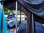 24 OCTOBER 2017 - BANGKOK, THAILAND: People wait to enter the royal cremation site, while their clothes, drenched in an overnight monsoon storm, dry on a crowd control barrier. People started camping out along Atsadang Road in Bangkok near the royal cremation site on Monday. The gates won't open until Wednesday morning and the cremation isn't until Thursday night, so most people will sleep outside, on sidewalks and footpaths for three nights. Hundreds of thousands of people are expected to try to get into Sanam Luang, the site of the cremation of Bhumibol Adulyadej, the Late King of Thailand, but the site will only hold about 60,000 people. The Thai government has built replica crematoriums around Bangkok to accommodate the overflow crowds.        PHOTO BY JACK KURTZ