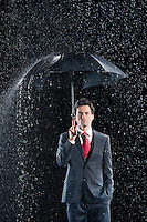 Businessman standing under sturdy Umbrella hand in pocket