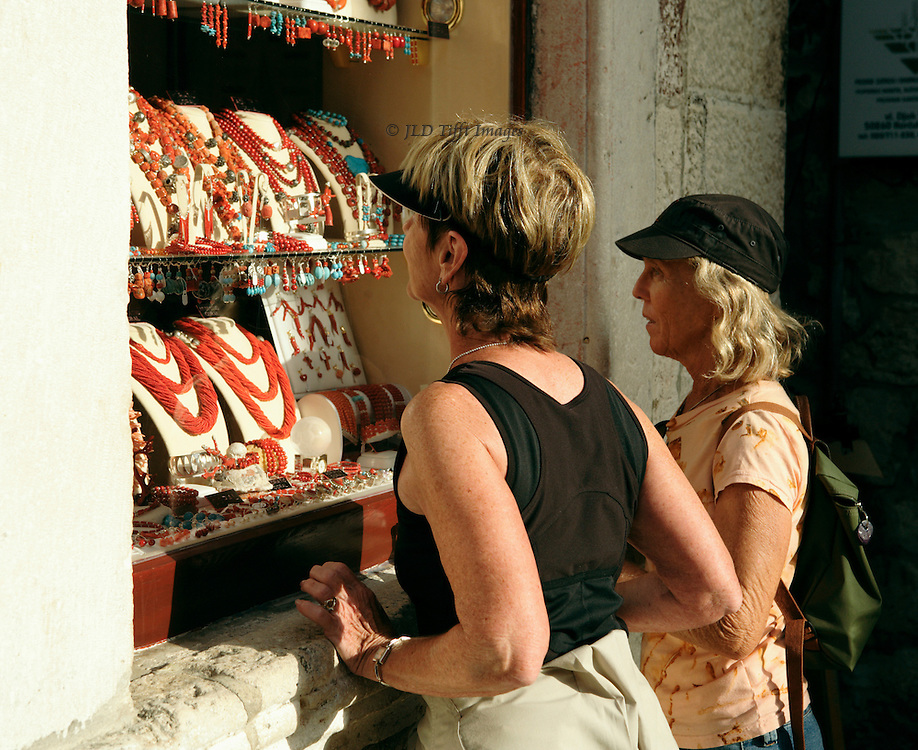 Two visiting adult women pause to look in the display window of a Korcula jewelry shop.  Afternoon sun sharply illuminates the necklaces shown.