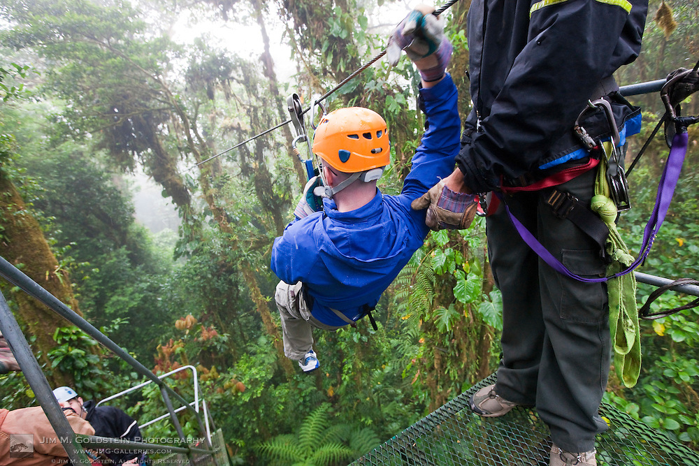 A young man embarks on a zip line through the rainforest canopy in the Monteverde Cloud Forest Reserve in Selvatura Adventure Park, Costa Rica