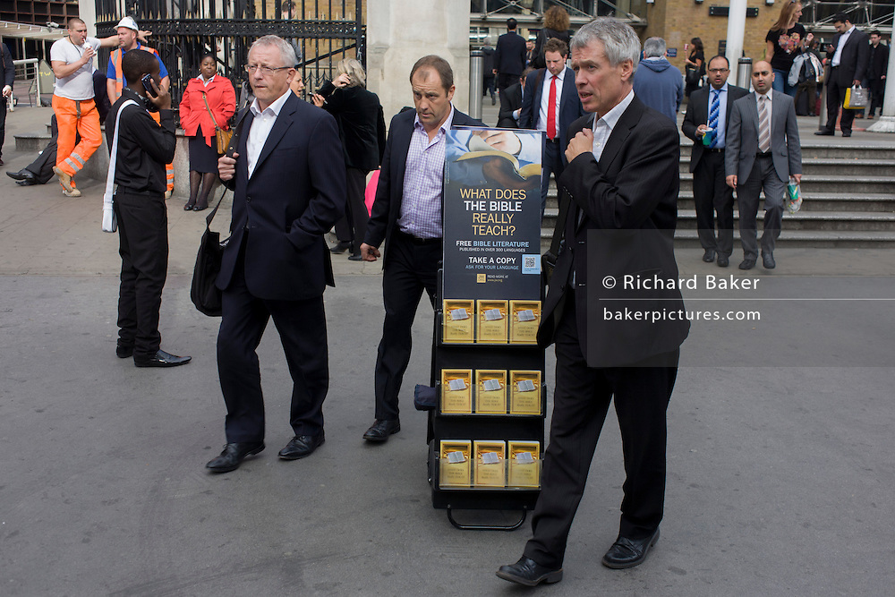Passers-by and a mobile rack of Jehova's Witness pamphlets outside Liverpool Street station, City of London.