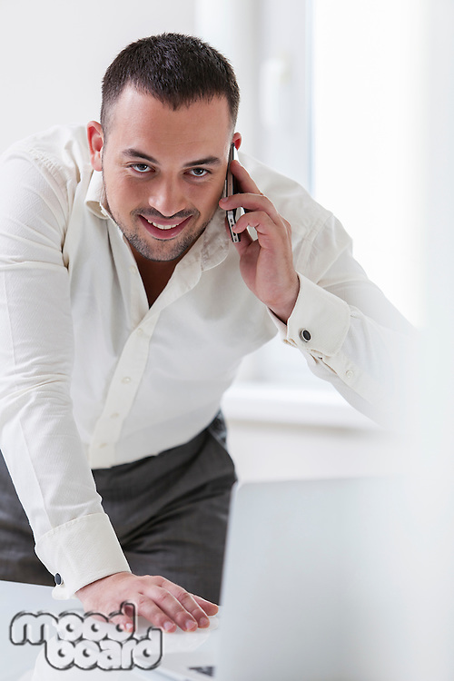 Businessman using mobile phone and looking at computer
