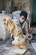 Village of Du Du specialized in manufacturing of woodcarving. Here a worker taking care of the finishing