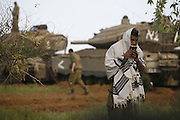 An Israeli soldier prays in front of a tank at a staging area near Israel's border with the Gaza Strip, in southern Israel, Tuesday, Dec. 30, 2008.