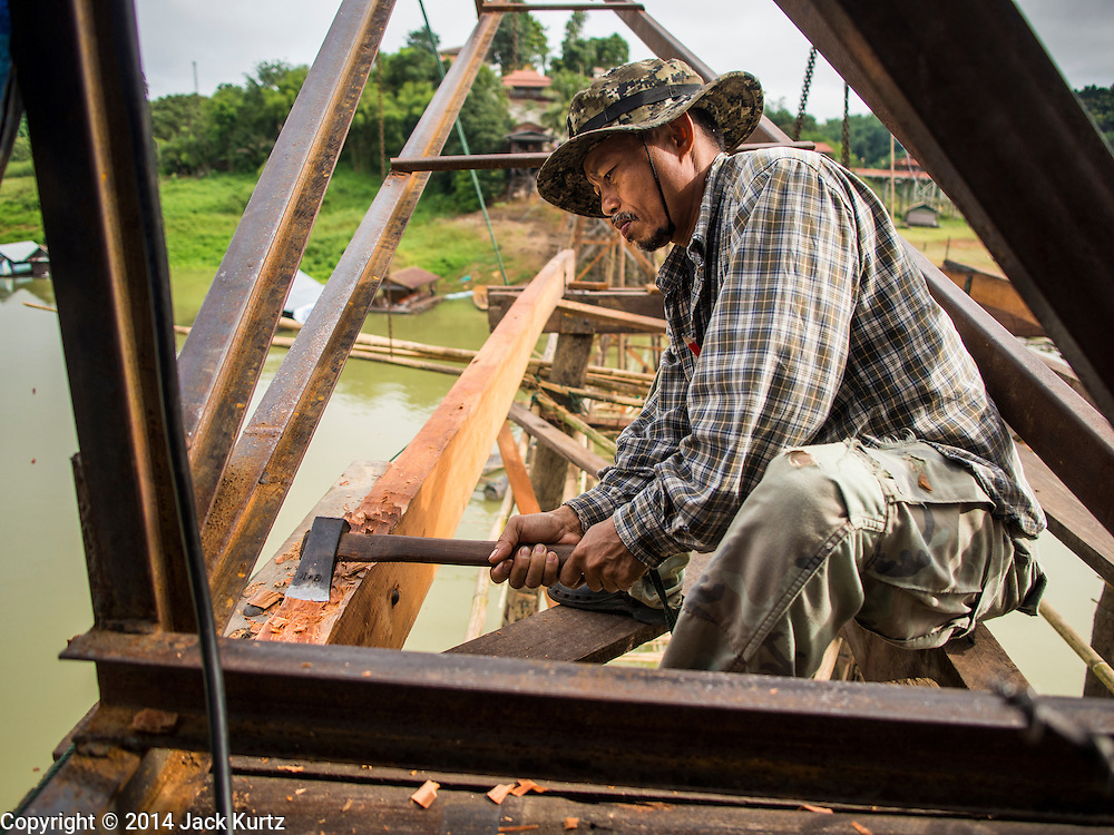 16 SEPTEMBER 2014 - SANGKHLA BURI, KANCHANABURI, THAILAND: A member of the Mon community cuts a piece of wood to fit as a pylon on the rebuilt Mon Bridge. The 2800 foot long (850 meters) Saphan Mon (Mon Bridge) spans the Song Kalia River. It is reportedly second longest wooden bridge in the world. The bridge was severely damaged during heavy rainfall in July 2013 when its 230 foot middle section  (70 meters) collapsed during flooding. Officially known as Uttamanusorn Bridge, the bridge has been used by people in Sangkhla Buri (also known as Sangkhlaburi) for 20 years. The bridge was was conceived by Luang Pho Uttama, the late abbot of of Wat Wang Wiwekaram, and was built by hand by Mon refugees from Myanmar (then Burma). The wooden bridge is one of the leading tourist attractions in Kanchanaburi province. The loss of the bridge has hurt the economy of the Mon community opposite Sangkhla Buri. The repair has taken far longer than expected. Thai Prime Minister General Prayuth Chan-ocha ordered an engineer unit of the Royal Thai Army to help the local Mon population repair the bridge. Local people said they hope the bridge is repaired by the end November, which is when the tourist season starts.    PHOTO BY JACK KURTZ