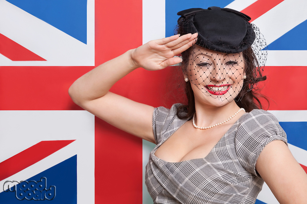 Portrait of young Caucasian woman with veiled hat saluting against British flag