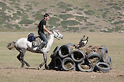 Man scores a goal by throwing a decapitated goat carcass into the circle of tyres and turf during a game of individual kok boru, a popular Central Asian horseback sport. Bosogo jailoo, Naryn province, Kyrgyzstan.