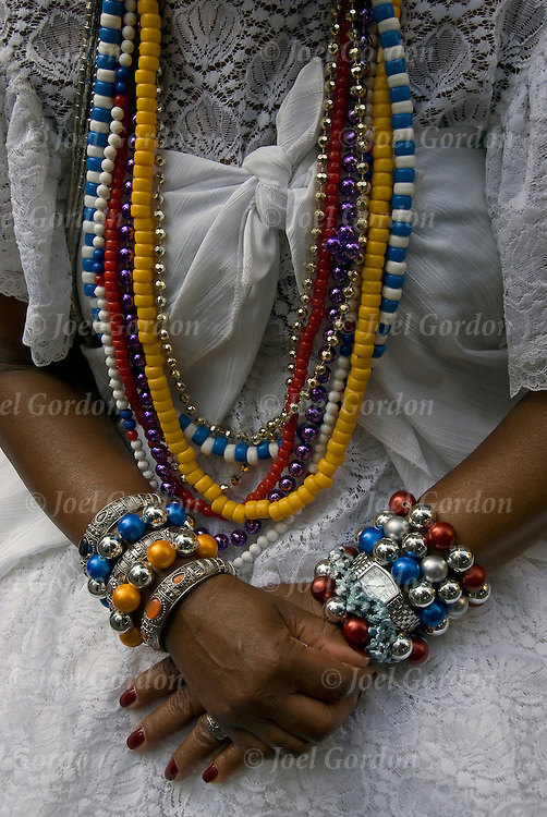 Close up of Bahiana American originally from Bahia, Brazil with colorful beads,  bracelets, rosaries, and necklaces.<br /> <br /> Lavagem da Rua 46, the religious blessing purification ritual performed to purity, energize the ground and the Bahianas performers.<br /> <br /> The base elements of water, flowers and perfumes white they dance in traditional, pure white skirts, blouses and headpieces adorned by numerous colorful beads, bracelets, necklaces and rosaries in honor of the the saints, while carrying vases filled with flowers. <br /> <br /> The result of the ritual is the peace, purification and energizing of all people.