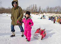 Amanda and Sophia Calley walk up the sledding hill with Sophia's Pink Monster Truck during Laconia Parks and Recreation Cardboard Sled Derby held Thursday afternoon at Memorial Hill.  (Karen Bobotas/for the Laconia Daily Sun)