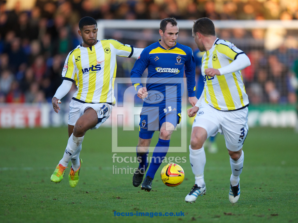 Picture by Alan Stanford/Focus Images Ltd +44 7915 056117<br /> 11/01/2014<br /> Luke Moore of AFC Wimbledon takes the ball between Joss Labadie (L) and Kevin Nicholson of Torquay United during the Sky Bet League 2 match at the Cherry Red Records Stadium, Kingston.