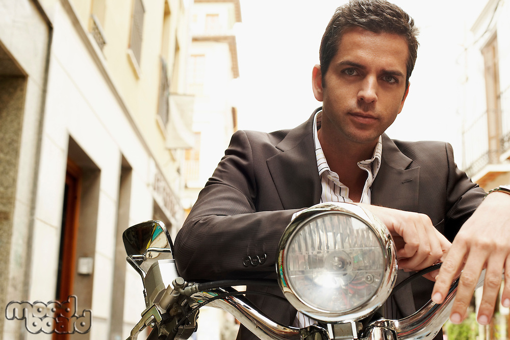 Man wearing suit sitting on motorcycle front view portrait.