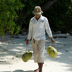 Boy carrying young coconut across a beautiful white sandy beach.