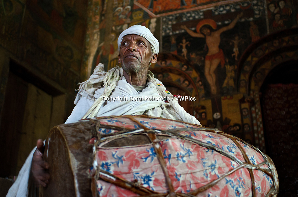 Debre Berhan Selassie Church in Gonder, Ethiopia. A priest plays the drum inside the church Debre Birhan Selassie (also called the Cherubim.) On the outskirts of the city of Gondar is the church Debre Birhan Selassie well known for its mural paintings, is located on a hill above The city, with beautifully painted walls that tell many religious stories.If you look up you see the eighty winged heads of Ethiopian cherubs smiling, all with a slightly different expression.It is the most famous roof of Ethiopia.