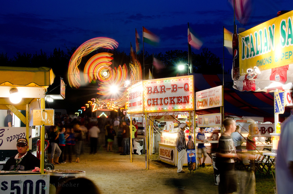 Fairground rides and food stalls at night, Blue Hill Fair, Maine.